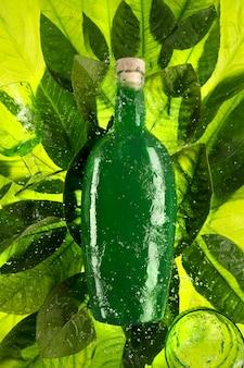 물과 함께 녹색 잎에 보드카와 녹색 유리잔을 넣은 녹색 병