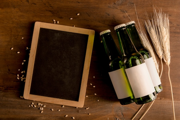 Green bottles with white label and blackboard on wooden table