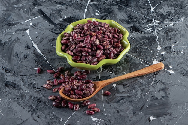 돌 표면에 생 콩으로 가득 찬 녹색 그릇.