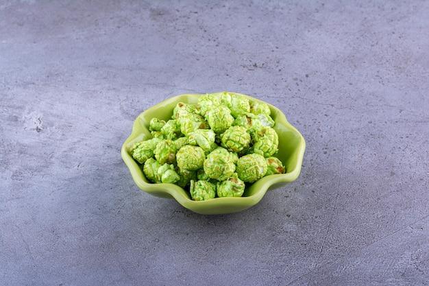 Ciotola verde che tiene un mucchio modesto di popcorn ricoperto di caramelle sulla superficie di marmo