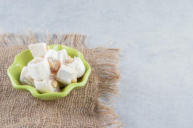 돌 배경에 견과류와 함께 맛있는 녹색 그릇을 취급합니다.