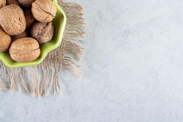 Зеленая чаша сырых грецких орехов на каменном фоне.