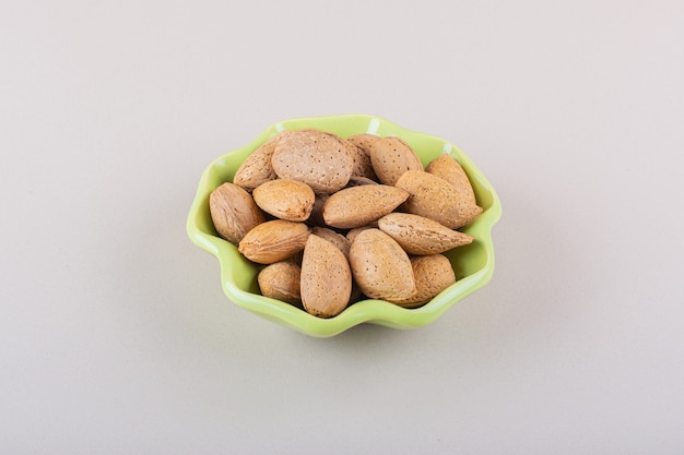 Green bowl of shelled organic almonds on white surface. high quality photo