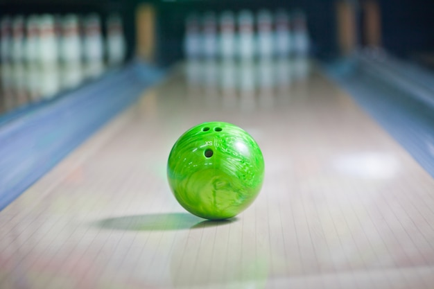 Green bowling ball put on alley with blurred bowling pin