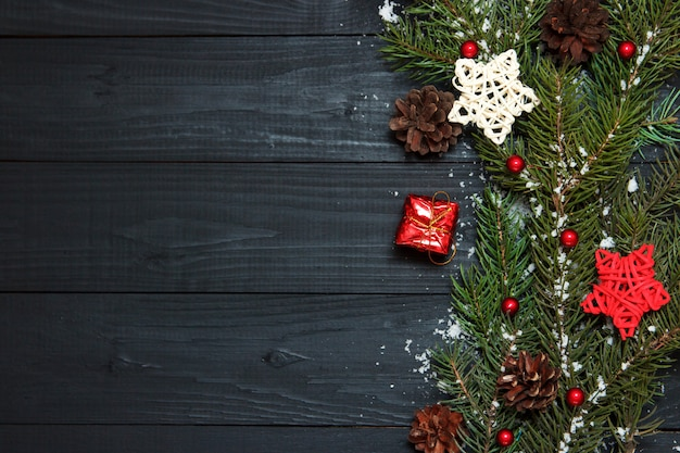 Green branches of a christmas tree with pine and toys on a black wooden background. copy space, flat lay.