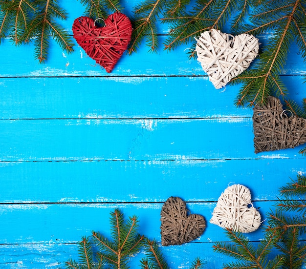 Green branches of needles and decorative wicker hearts on a blue wooden background