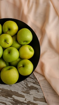 Зеленые яркие яблоки на черной тарелке и бежевой ткани