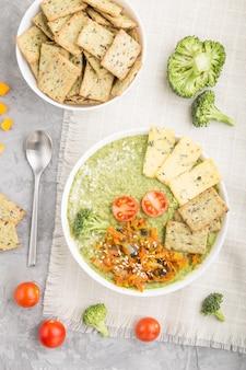 灰色のコンクリート背景、上面に白いボウルにクラッカーと緑のブロッコリークリームスープ。