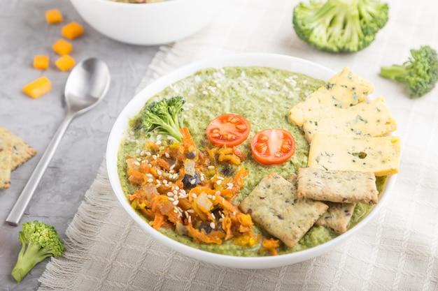 白いボウル、サイドビューのクラッカーと緑のブロッコリークリームスープ