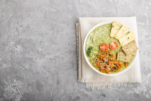 白いボウル、平面図、copyspaceのクラッカーと緑のブロッコリークリームスープ。