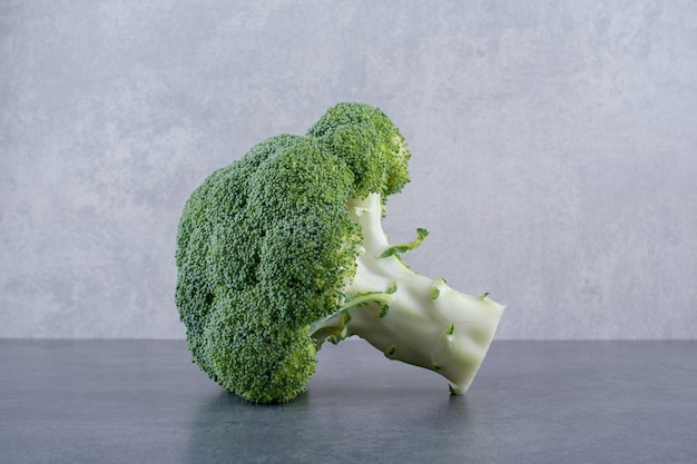 Green broccoli isolated on concrete background.