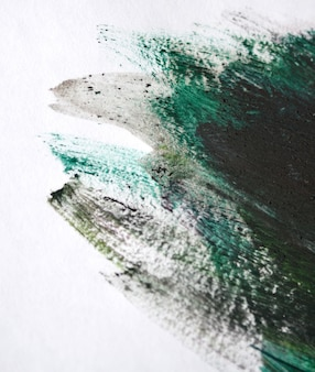 緑のブラシは白い紙に油絵の具を撫でます。白い背景で隔離。抽象的な創造的な背景