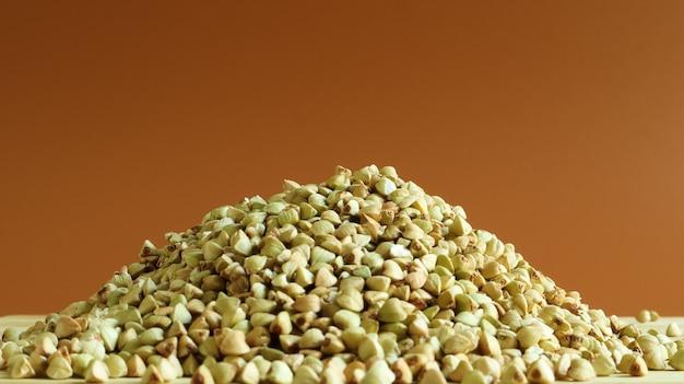 Зеленые семена гречихи на деревянных фоне. отличная еда. здоровая крупа. органические сырые необжаренные вегетарианские блюда. концепция здорового, сбалансированного и диетического питания. скопируйте пространство.