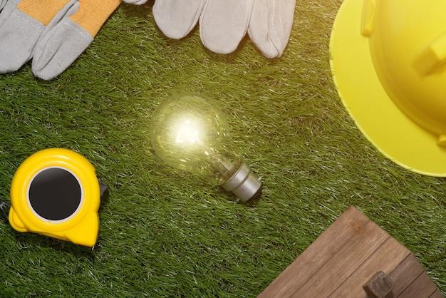 Концепция экологичного строительства и энергосбережения: проект дома и рабочие инструменты на траве