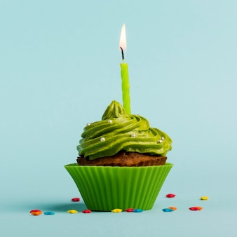 Green burning candles on decorative muffins with colorful star sprinkles against blue backdrop