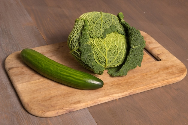 Green cabbage and cucumber lie on a chopping board