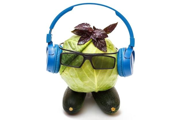 青いスタイリッシュなヘッドフォンと白い背景で隔離のサングラスの緑のキャベツの頭。菜食主義。音楽を聴く