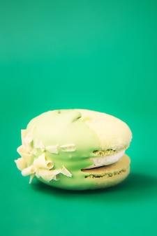 Зеленый торт макарон или миндальное печенье на зеленой стене. разноцветное миндальное печенье. французский макарун торт