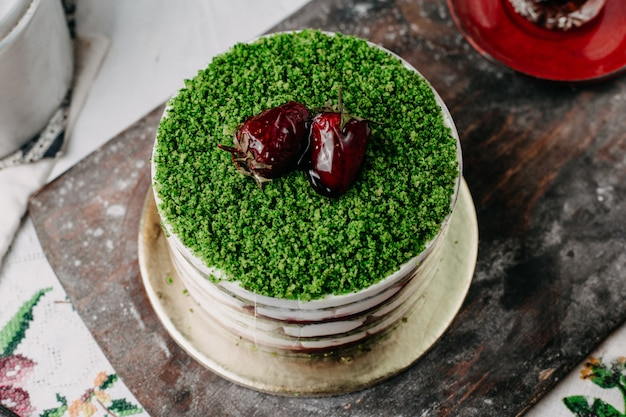 Green cake powdered fruit cake with sliced fruits round yummy delicious on grey desk