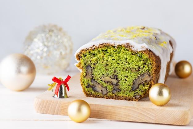 明るい背景にほうれん草のクルミとクリスマスボールとレモンの緑のケーキ