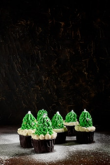Green cakes with the addition of white cream in the form of christmas trees are in different order sprinkled with powdered sugar