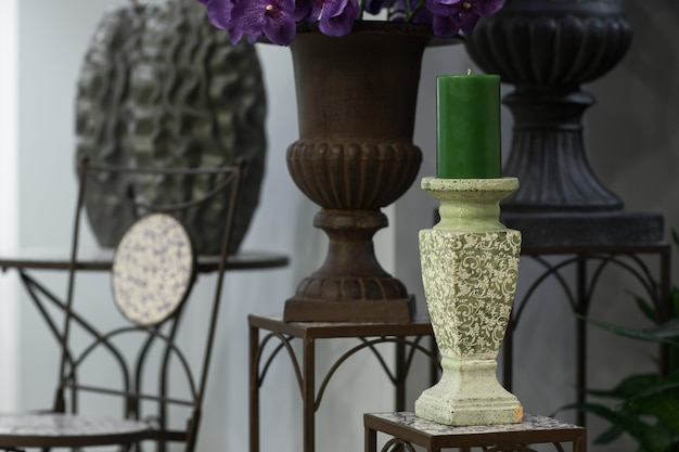 Green candle on a candlestick on the marble background of flowers and vases