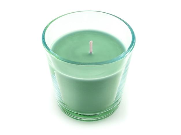 白い背景の上のガラスの燭台の緑のキャンドル