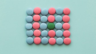 Green candy arranged in the pink and blue candies on colored background