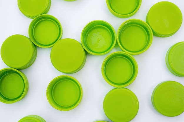 Green caps from plastic bottles on white background flat lay