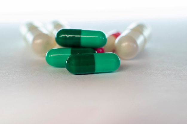 배경이 흐릿한 조작된 약의 녹색 캡슐