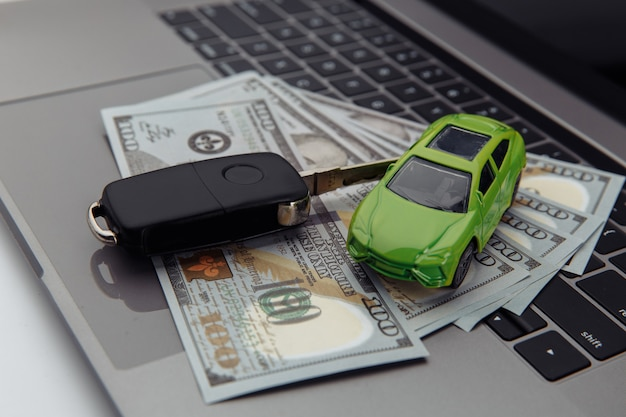 緑の車とドル紙幣のクローズアップの鍵。オンライン購入車のコンセプト