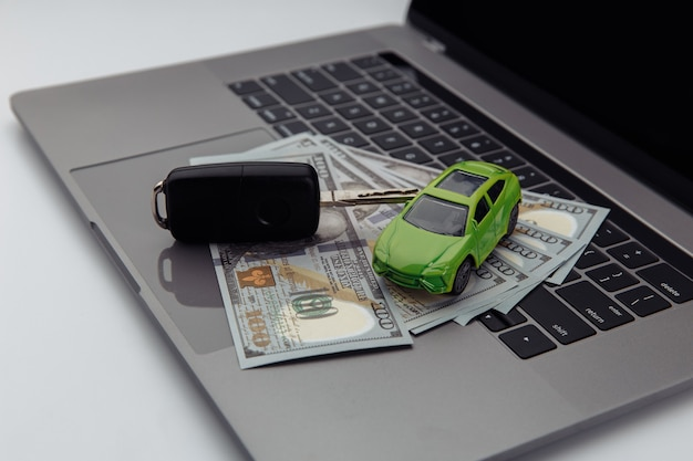 Green car and keys with dollar banknotes and shopping cart on keyboard
