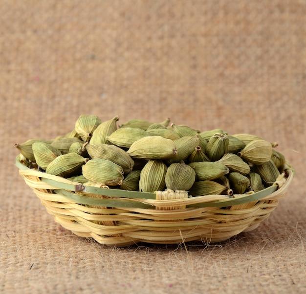 Стручки зеленого кардамона в бамбуковой корзине на мешковине