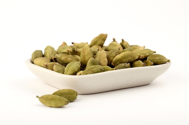 Green cardamom pods in plate