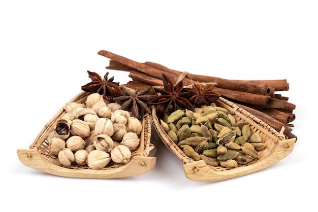 緑のカルダモン、サイアムカルダモン、スターアニス、シナモンの樹皮が白で分離されています。