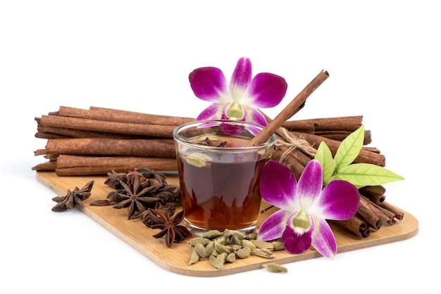 緑のカルダモン、サイアムカルダモン、スターアニス、シナモンの樹皮と白で分離されたお茶。