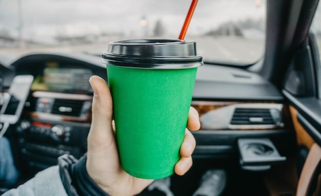 手に車の中でコーヒーの緑の段ボールカップは旅行で飲む