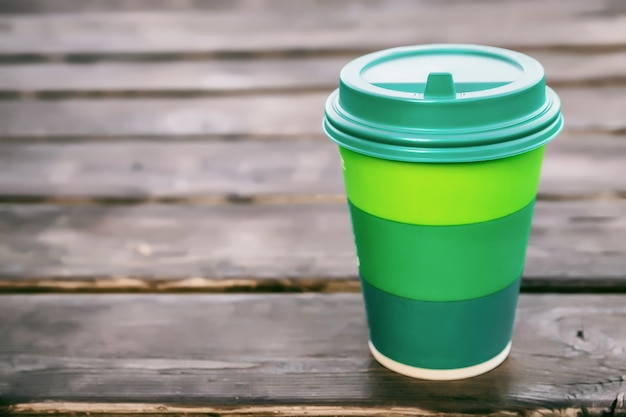Зеленая картонная чашка с пластиковой крышкой для кофе на деревянном фоне, место для copyspace, крупным планом