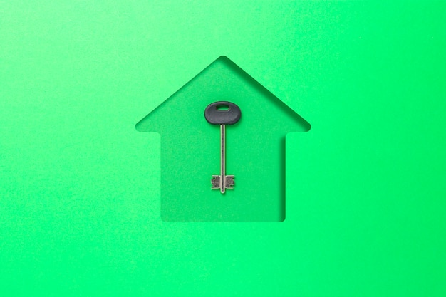 Green cardboard cut in the shape of a house and key.