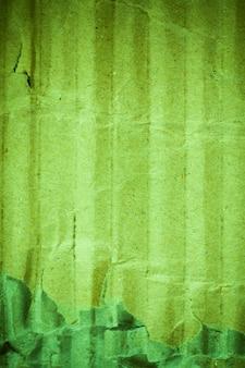 緑の段ボール紙の背景のビネット。