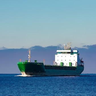Зеленый грузовой корабль движется в стоячей воде балтийского моря