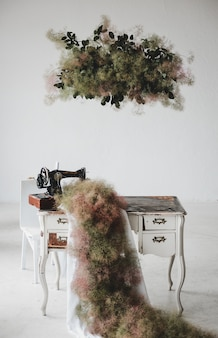 Green carpet hangs from the sewing machine on a table