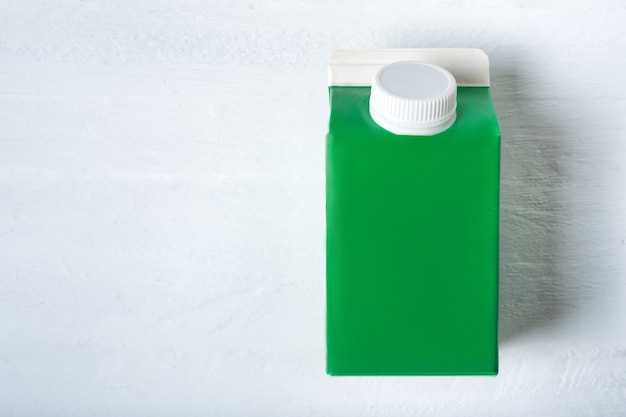 Green carton box or packaging of tetra pack with a cap.