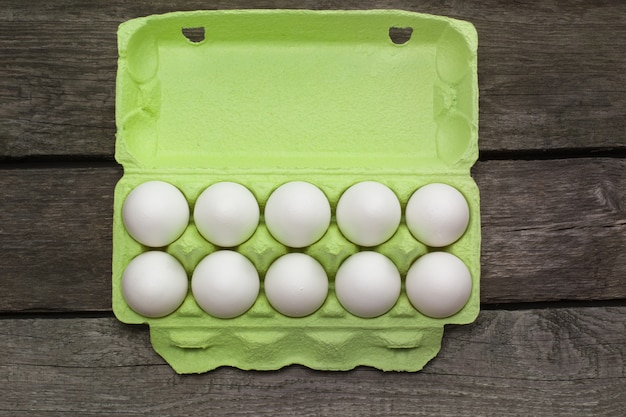 Green carton of organic eggs on wooden board. top view.