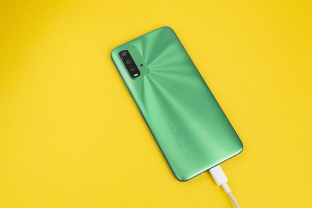 Зеленый сотовый телефон, подключенный к usb-кабелю типа c - зарядка