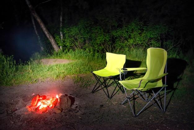 夜の焚き火の近くの緑の椅子。キャンプの暖炉