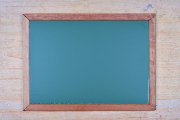 木製の背景に緑の黒板