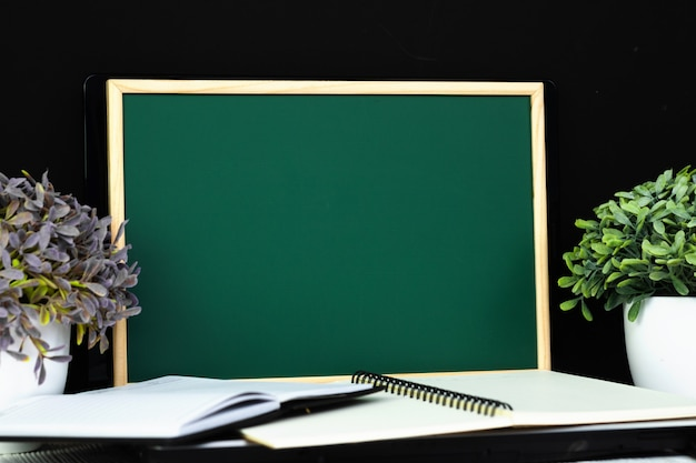 Green chalkboard with pile of notebook pape