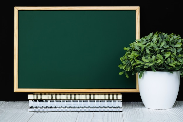 Green chalkboard with pile of notebook paper, stationery or school supplies.