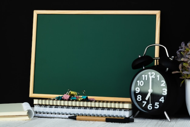 Green chalkboard with pile of notebook paper